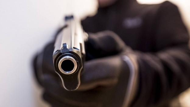 Schwarz gekleidete Person zielt mit Waffe auf Bildbetrachter