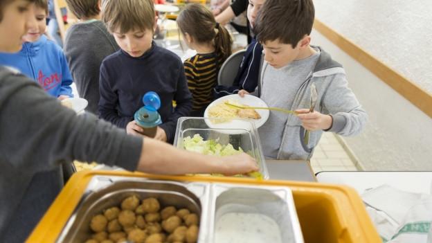 Schulkinder schöpfen sich das Mittagessen.
