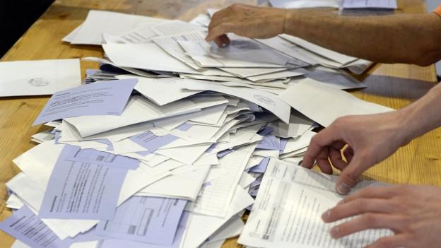 Eine grosser Haufen voller ausgefüllter Wahlzettel liegt auf einem Tisch.