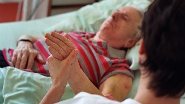 Ein Mann in einem Spitalbett, eine Frau hält seine Hand.