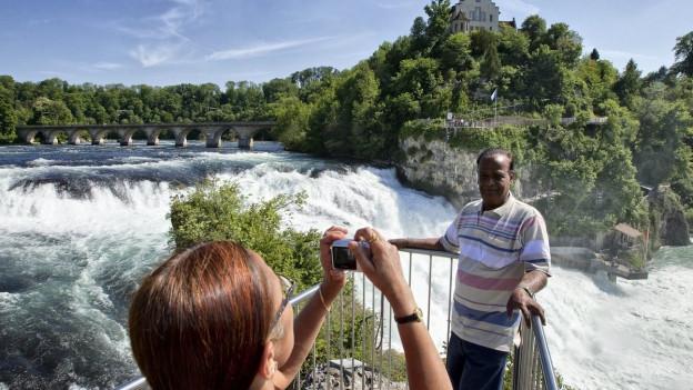 Touristen knipsen ein Foto vor dem Rheinfall.