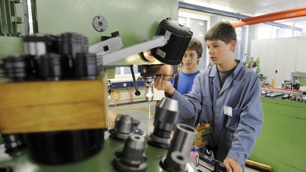 Zwei Polymechaniker-Lehrlinge bei der Arbeit.