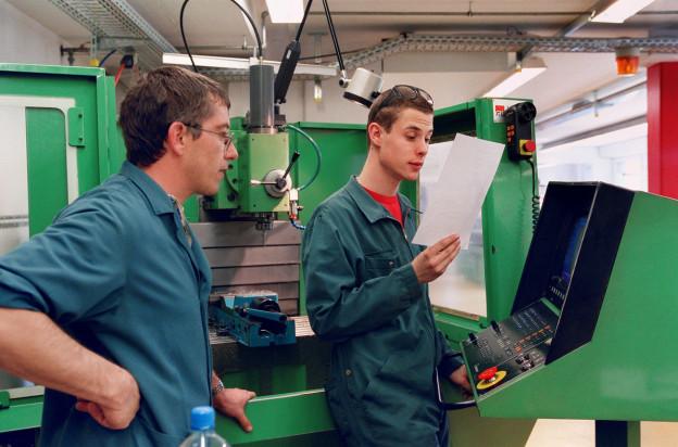 Ein Lehrmeister instruiert einen Lehrling an einem Apparat.