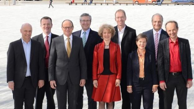 Sieben Männer und zwei Frauen stehen auf einem Platz