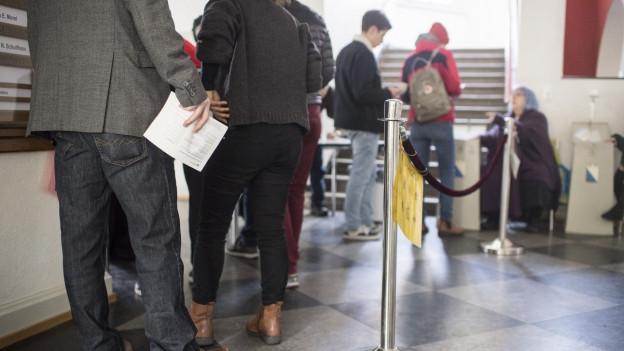 Menschen stehen im Abstimmungslokal Schlange