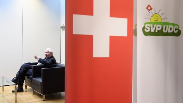 CB sitzt im Hintergrund auf eine Sofa, im Vordergrund eine Schweizerfahne und das Logo der SVP