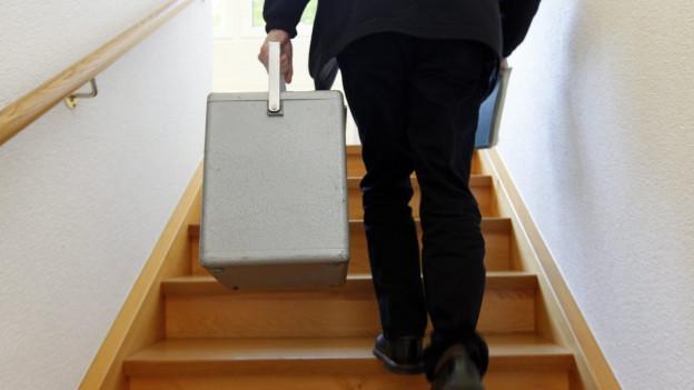 Ein Mann trägt eine Wahlurne die Treppen hoch.