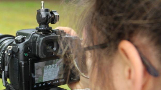 Eine Jugendliche bedient eine Videokamera