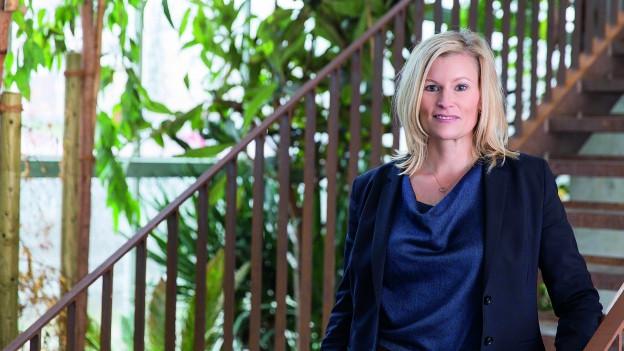 Eine Frau mit blonden Haaren und in blauem Jacket