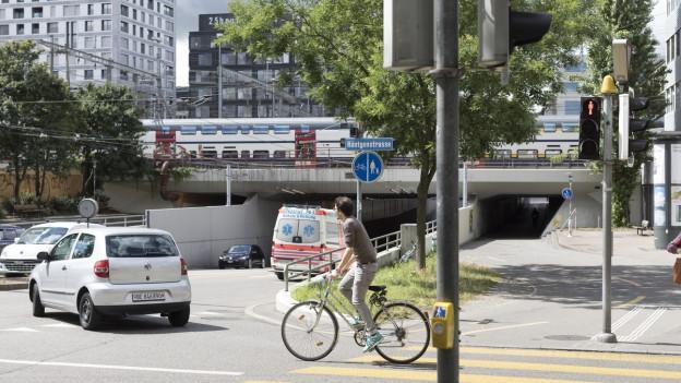 Eine Strasse mit Autos und Velofahrer, dahinter ein Zug.