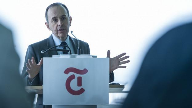 Mann steht hinter einem Rednerpult