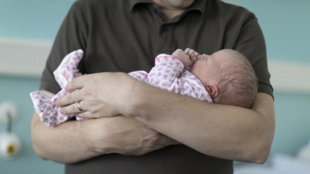 Ein Mann hält ein kleines Baby in seinen Armen.