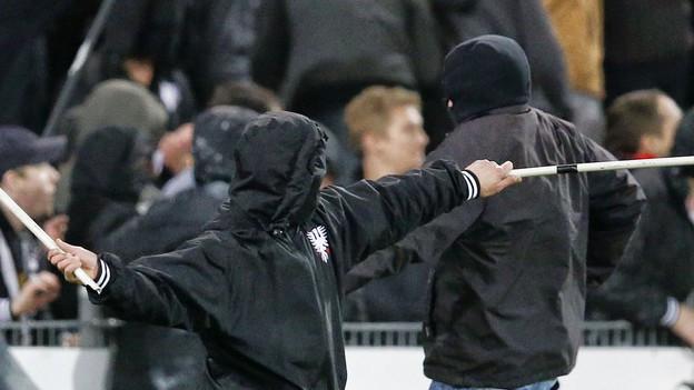 Prügelnde Fans in einem Fussballstadion