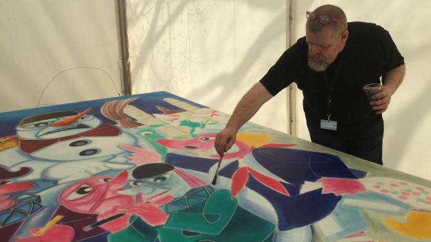 Laternenmaler Christoph Knöll bringt Farbe auf seinem Sechseläuten-Sujet an.