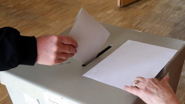 Wahlzettel wird in eine Wahlurne geworfen.