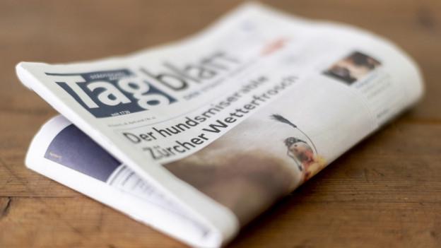 Eine Zeitung liegt auf einem Holztisch