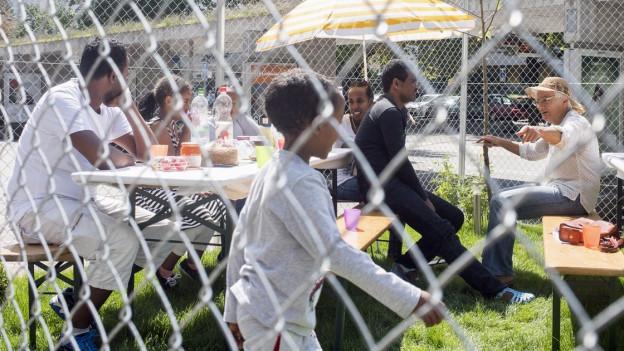 Eine Gruppe Asylsuchender sitzt um einen Tisch im Freien.