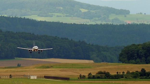 Ein Flugzeug landet, dahinter Hügel und Bäume