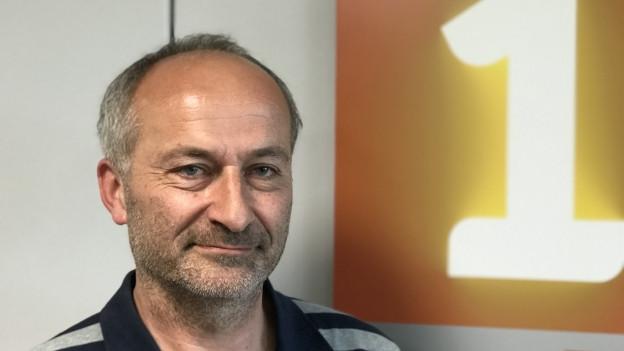 """Mann mit Dreitagebart neben Logo """"SRF 1"""""""