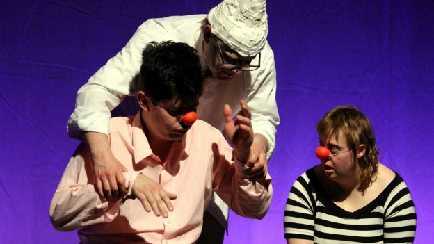 Zwei Männer und eine Frau mit Clown-Nasen auf einer Bühne