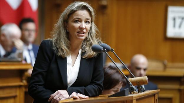 Eine Frau mit blonden, halblangen Haaren, in weisser Bluse und schwarzer Jacke steht an einem Rednerpult.