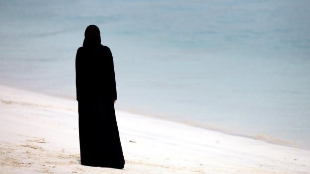 Eine Frau im Tschador am Strand