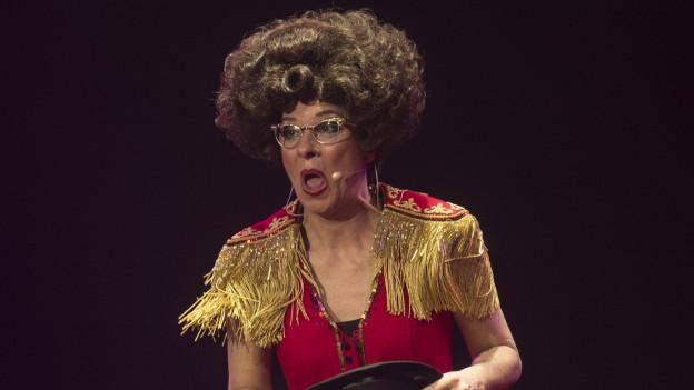 Eine Frau mit lockiger Perücke, dicker Brille und in einem Zirkuskostüm.