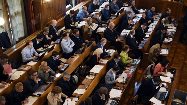Frauen und Männer sitzen in einem Ratssaal.