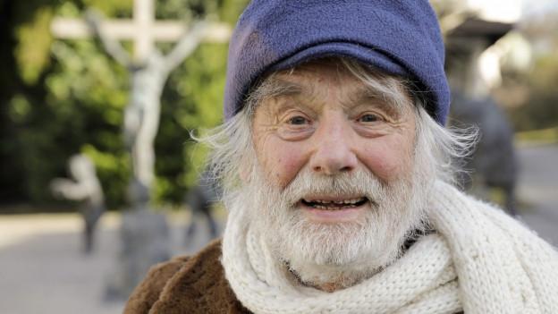 Ein alter Mann mit weissem Bart, Mütze und Schal