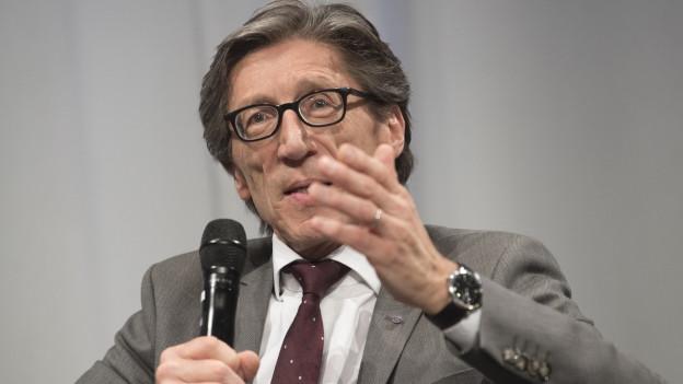 Ein Mann mit Brille spricht in ein Mikrofon
