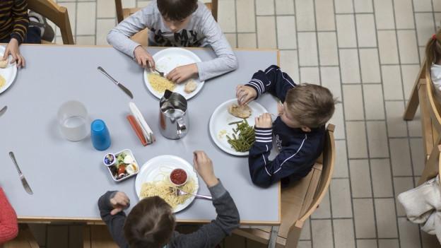 Kinder sitzen an einem Tisch beim Mittagessen.