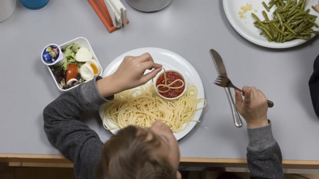 Ein Kind sitzt an einem Schultisch und isst einen Teller Spaghetti.