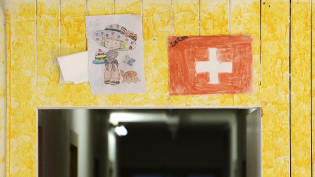 An einer Holzwand hängt eine selbst gemalte Schweizer Flagge.