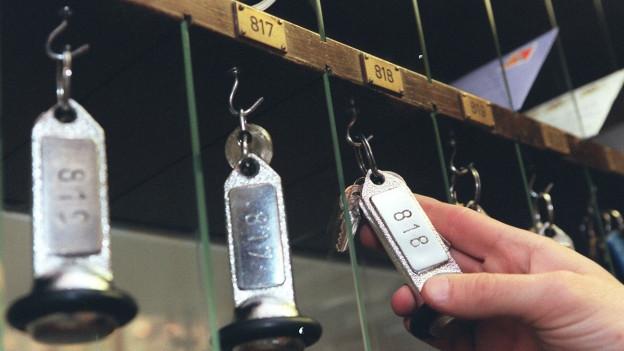 Eine Hand nimmt einen Hotelschlüssel vom Haken