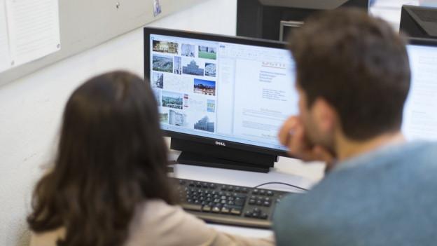 Ein Lehrer und eine Schülerin vor einem Computer-Bildschirm