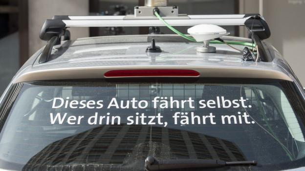 """Ein Auto, auf der Scheib steht: """"Dieses Auto fährt selber. Wer drin sitzt, fährt mit."""""""