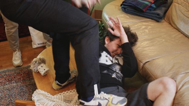 Ein Mann verprügelt einen Jungen.