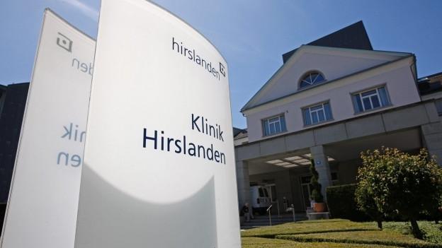 """Eingang zu einer Klinik, Tafel mit Aufschrift """"Hirslanden"""""""