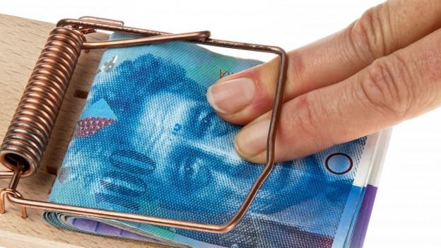 Eine Mausefalle schnappt zu beim Versuch, Geldscheine daraus zu entfernen.