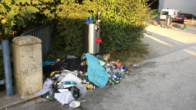 Vor einem Abfalleimer liegt überall Abfall herum.