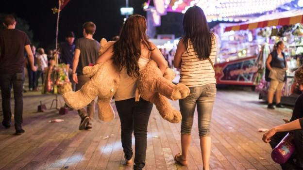 Zwei junge Frauen laufen abends über ein Festgelände mit grossen Plüschtieren in der Hand.