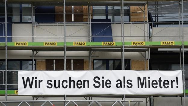 """Ein Haus mit Baugerüst, darauf steht: """"Wir suchen Sie als Mieter""""."""