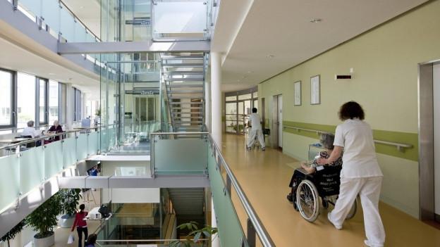Spitalgänge, Frau im Rollstuhl wird von Pflegerin geschoben