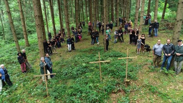 Frauen, Männer und Kinder sind in einem Wald an Bäume angebunden.
