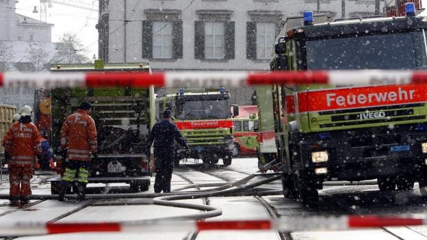 Vier Feuerwehrautos stehen auf einer Strasse.