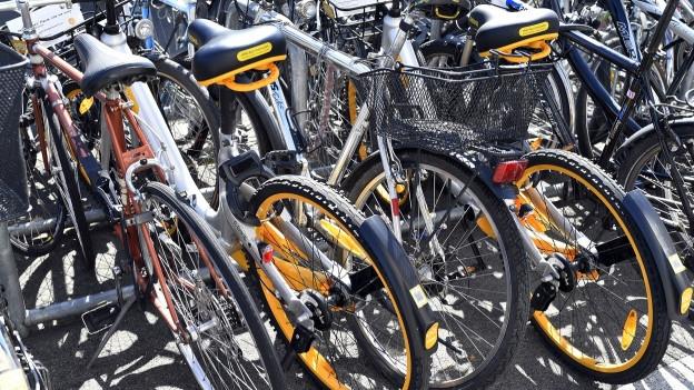 gelbe O-Bikes zwischen anderen Velos in öffentlichem Veloständer