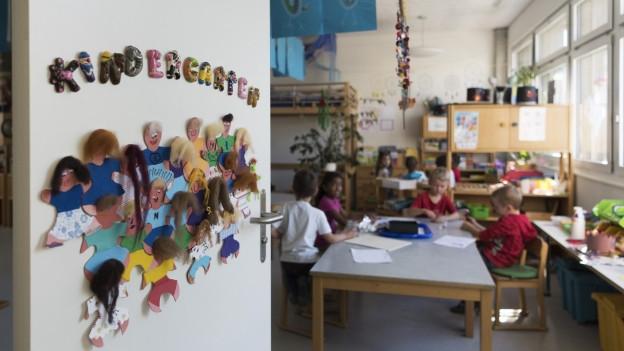 In einem Klassenzimmer sitzen Kinderhartenschülerinnen und -Schüler an den Tischen.