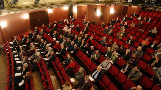 Blick in Zuschauersaal eines Theaters mit roten Samtsesseln