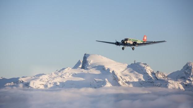 altes Flugzeug fliegt über Schneeberge vor blauem Himmel