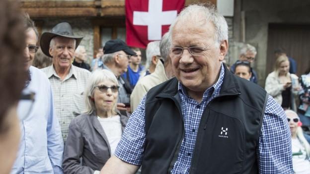 Bundesrat Johann Schneider-Ammann begrüsst eine Person.